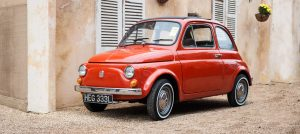 An automotive photograph showing a small car, a Fiat 500 on location.