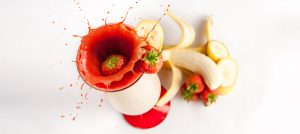 Product Food and Drink photograph of a strawberry splashing into a smoothie