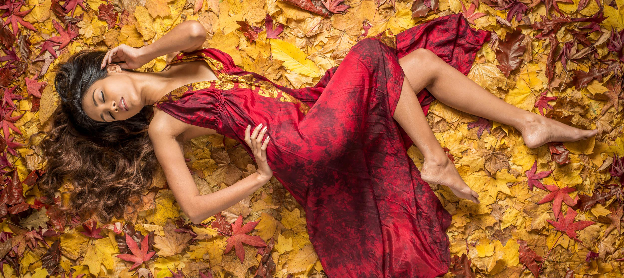 Fashion Photographers image of a model in a red silk dress on a background of autumn leaves