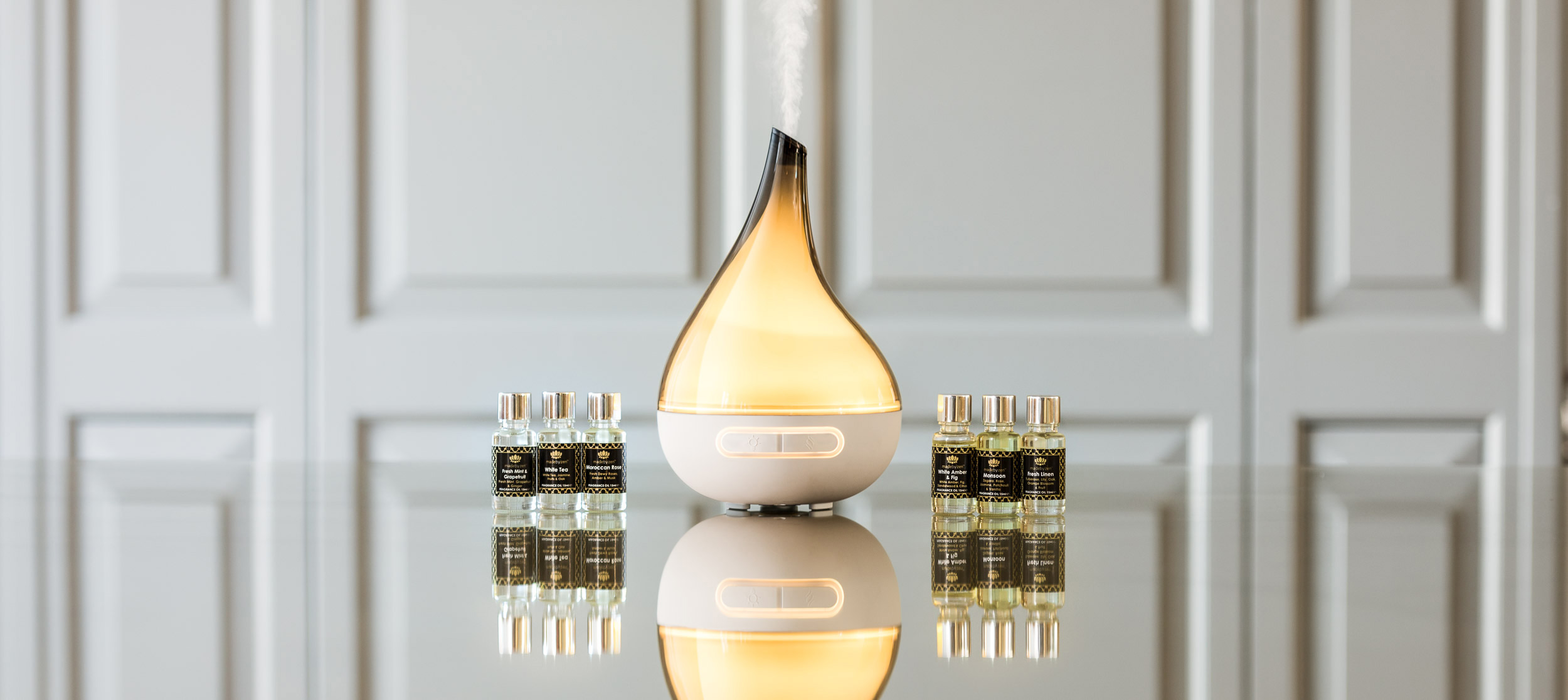 Product Photography of an oil diffuser and oils on a reflective surface.